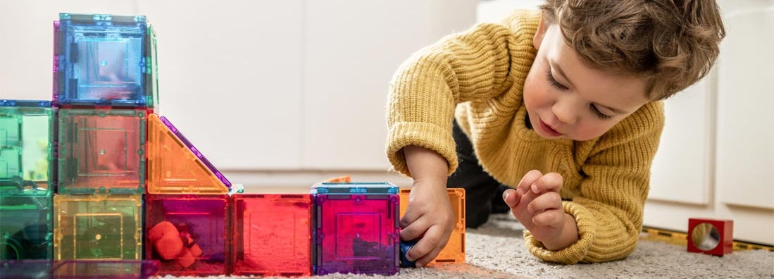 Child playing with magnetic bright multicolored tiles. Find daycare insurance.