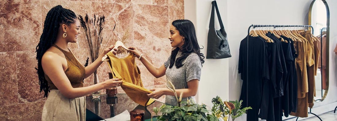 Young woman making a purchase in a fashion store. Find Retail Insurance.