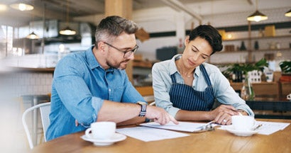 Business owners going through insurance paperwork together in their coffee shop