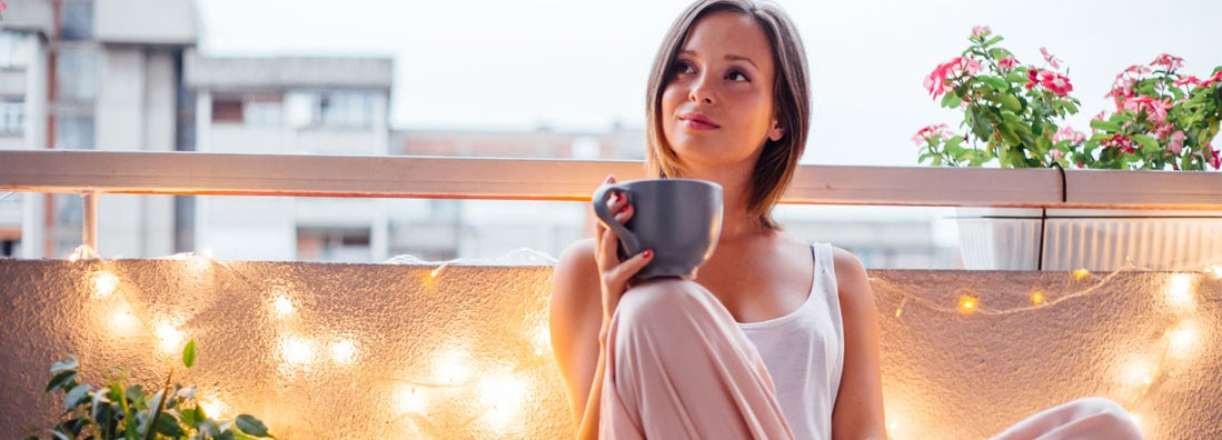 enjoying a cup of coffee on a lit balcony
