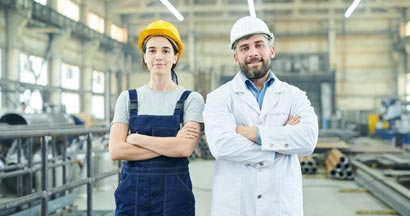 Two modern factory workers looking at camera while posing in industrial workshop