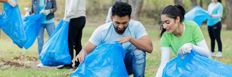 Volunteers in public park participating in community cleanup day. Find nonprofit insurance.