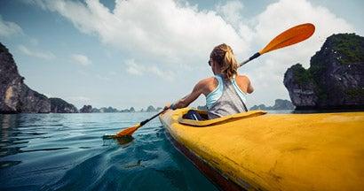 Woman exercising and exploring calm tropical bay by kayak.