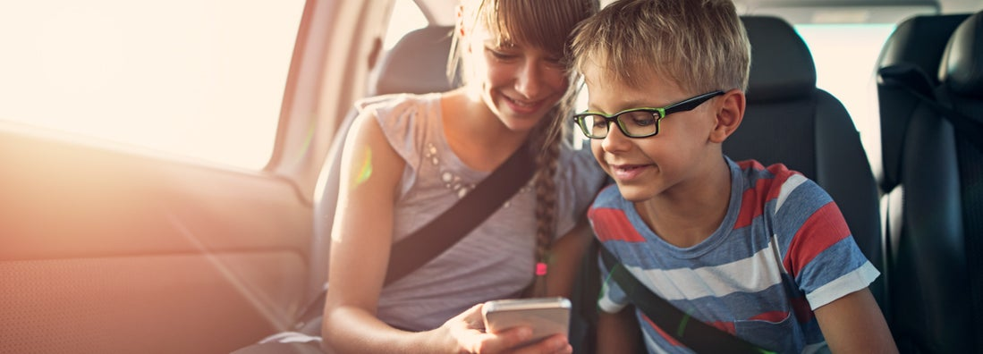 Kids playing smartphone during a road trip