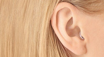 blonde Frau trägt ein In-Ohr-Hörgerät