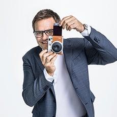 Robert F. Hartluaer mit Sofortbildkamera