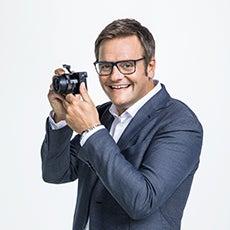 Robert F. Hartlauer mit Kamera seitlich