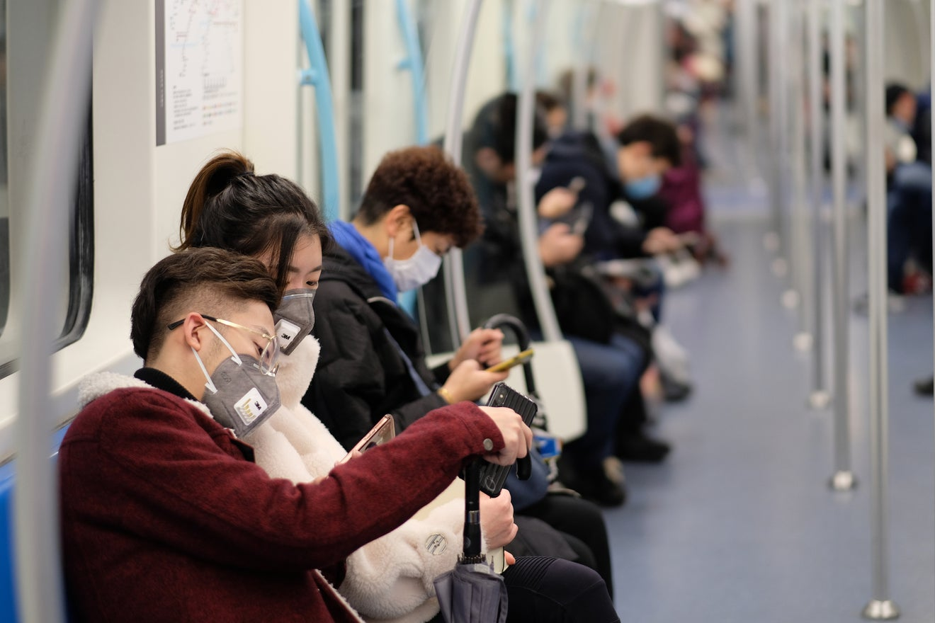 Coronavirus fears: a family wearing surgical mask waiting at bus station in Shanghai